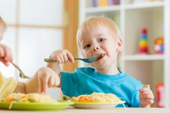 Kid boy eating spaghetti in nursery Royalty Free Stock Photo