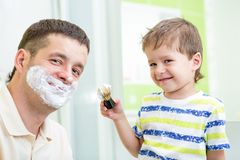 Kid boy and father having fun in bathroom. At shaving Royalty Free Stock Image