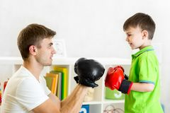 Kid boy and father play boxing Stock Photo