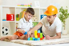 Kid boy and father play builders. In nursery at home royalty free stock image