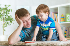 Kid boy and father read a book on floor indoors Stock Photography
