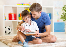 Kid boy and father read a book on floor indoors. Kid boy and his father read a book on floor indoors stock photography