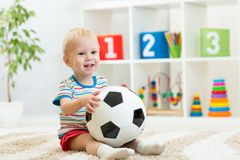 Kid boy with football  indoor Royalty Free Stock Image
