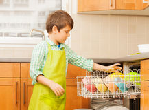 Kid boy getting out clean crockery of dishwasher. Kid boy in apron getting out clean and dry crockery of dishwasher in the kitchen stock photo