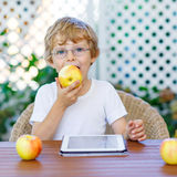 Kid boy with glasses playing with tablet and eating apple Royalty Free Stock Images