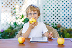 Kid boy with glasses playing with tablet and eating apple Royalty Free Stock Photos