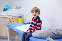 Kid boy with glasses waiting for check-up of Royalty Free Stock Image