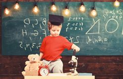 Kid boy in graduate cap near microscope in classroom, chalkboard on background. First former interested in studying royalty free stock images