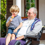 Kid boy and grandfather on wheelchair eating ice cream Royalty Free Stock Photos