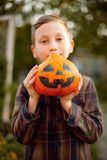 Kid boy with halloween pumpkin. Sunset light. royalty free stock photography