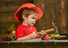 Kid boy hammering nail into wooden board. Child in helmet cute playing as builder or repairer, repairing or handcrafting. Handcrafting concept. Toddler on busy Stock Photo