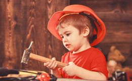 Kid boy hammering nail into wooden board. Child in helmet cute playing as builder or repairer, repairing or handcrafting. Toddler on busy face plays at home in stock photo