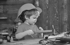 Kid boy hammering nail into wooden board. Handcrafting concept. Toddler on busy face plays at home in workshop. Child in. Helmet cute playing as builder or royalty free stock photography