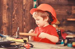 Kid boy hammering nail into wooden board. Handcrafting concept. Toddler on busy face plays at home in workshop. Child in. Helmet cute playing as builder or stock photo