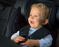 Kid boy happy in a car seat royalty free stock photo