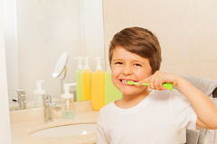 Kid boy happy to brush teeth in the morning. Portrait of happy kid boy brushing teeth in bath in the morning Royalty Free Stock Photography