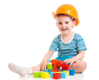 Kid boy in hard hat with colorful building blocks. Isolated Royalty Free Stock Photo