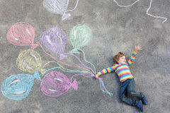 Kid boy having fun with colorful balloons drawing with chalks Stock Photos