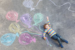 Kid boy having fun with colorful balloons drawing Royalty Free Stock Photo