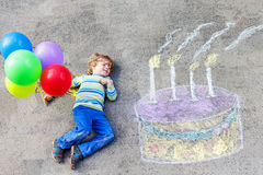 Kid boy having fun with colorful birthday cake drawing with chal. Happy little kid boy having fun with big birthday cake picture drawing with colorful chalks and Royalty Free Stock Photos