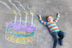 Kid boy having fun with colorful birthday cake drawing with chal. Happy little kid boy having fun with big birthday cake picture drawing with colorful chalks Royalty Free Stock Photo