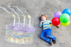 Kid boy having fun with colorful birthday cake. Happy little kid boy having fun with big birthday cake picture drawing with colorful chalks and balloons Royalty Free Stock Image