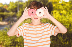 Kid boy having fun with donuts. Teenager boy holding two donuts outdoors have fun at green background Royalty Free Stock Photography