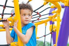 Kid boy having fun to play on children`s climbing toy at school playground,back to school activity.kindergarten preschool.  royalty free stock image