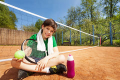 Kid boy having rest after playing tennis. Sitting on the clay court near the tennis net, holding racket and ball Royalty Free Stock Images