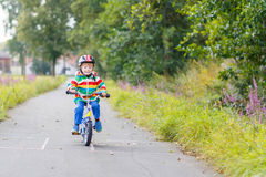 Kid boy in helmet riding his first bike, outdoors Royalty Free Stock Photos