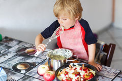 Kid boy helping and baking apple pie in home''s kitchen Stock Images