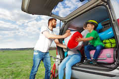 Kid boy helping his father to load their car boot. Kid boy helping his father to load their minivan after the summer vacation royalty free stock image