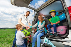 Kid boy helping his parents to load their car boot stock image