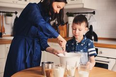 Kid boy helps mother to cook in modern white kitchen. Happy family in cozy weekend morning Royalty Free Stock Photo