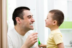 Kid boy and his dad cleaning teeth in bathroom. Child boy and his dad cleaning teeth in bathroom Stock Photography
