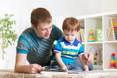 Kid boy and his dad read a book. Together Royalty Free Stock Photo