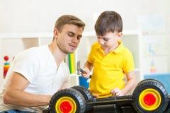 Kid boy and his dad repair toy car Stock Photos