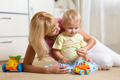 Kid boy and his mother repair toy car at home Royalty Free Stock Photo
