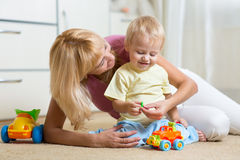 Kid boy and his mother repair toy car at home Royalty Free Stock Photos
