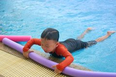 Kid or boy hold foam noodle on swimming pool side bar to float d stock images