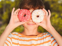 Kid boy holding donuts outdoors. Teenager boy holding pink glazed donut outdoors Stock Photos
