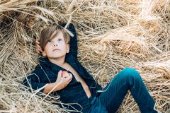 Kid boy holding gold leaf and lies on the hay. Sale for entire autumn collection, incredible discounts and wonderful. Choice. Back to school. Bye summer - hi stock photos