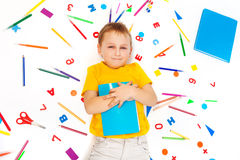Kid boy holding textbook laying among stationery Royalty Free Stock Photography