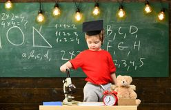 Kid Boy In Graduate Cap Near Microscope In Classroom, Chalkboard On Background. First Former Interested In Studying Royalty Free Stock Photos