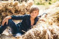 Kid boy lies on the hay. Boy in the hat are preparing for autumn sunny day. Cute boy are getting ready for autumn sale. Childhood in the farm. Good time in the royalty free stock images