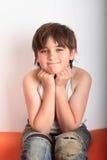 Kid - boy. Little kid - smiling boy - sitting on orange couch Royalty Free Stock Photo