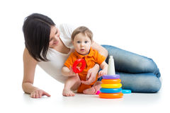 Kid boy and mother play together with pyramid toy Royalty Free Stock Photo