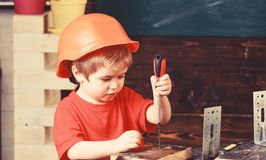 Kid boy in orange hard hat or helmet, study room background. Boy play as builder or repairer, work with tools. Childhood royalty free stock images