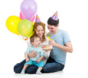 Kid boy with parents celebrating birthday  and blowing candles o Stock Photo