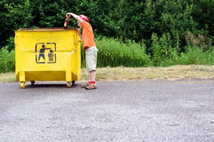 Kid or boy pick garbage and throw to litter can Stock Images